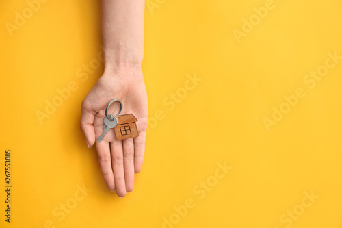 Photo  Female hand with key from house on color background