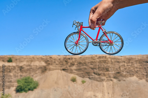 Papiers peints Velo red metal toy bike in the hands against the background of a cliff in the distance with an optical illusion of a big bike on a clear sunny day in summer while traveling