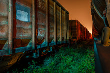 Freight Train Station At Night. Night Depot. Old Rusty Railroad Cars