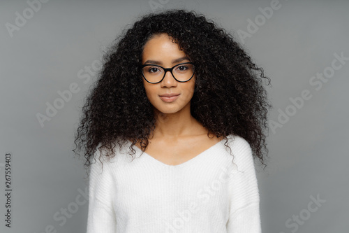 Fotografiet  Portrait of serious woman with dark skin, Afro bushy hair, wears big transparent glasses and white soft sweater, looks directly at camera, isolated over grey background