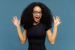Slim overemotive dark skinned woman raises hands, opens mouth, gestures actively from positive emotions, focused down, dressed in casual black t shirt, isolated over blue background. Ethnicity concept