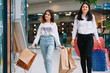 Beautiful young mom and teenage daughter are holding shopping bags, shopping in mall. Family shopping.