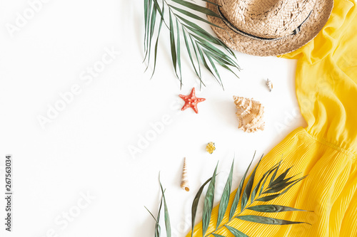 Summer composition. Tropical leaves, dress, hat on white background. Summer concept. Flat lay, top view, copy space