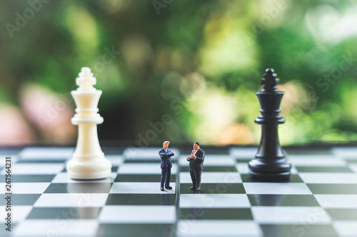 Fotografia, Obraz Miniature people businessmen standing on a chessboard with a chess piece on the back Negotiating in business