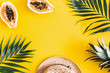Leinwandbild Motiv Summer composition. Tropical palm leaves, hat, fruits on yellow background. Summer concept. Flat lay, top view, copy space