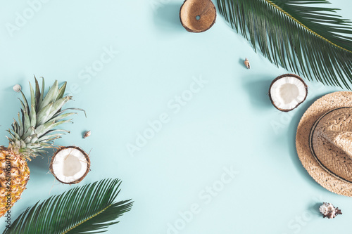 Summer composition. Tropical palm leaves, hat, fruits on blue background. Summer concept. Flat lay, top view, copy space
