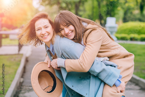 Fényképezés  Two adult playfull good looking women sisters in trendy coat piggybacking her pretty girlfriend in spring park outdoor