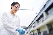 Serious Attractive Young Asian Laboratory Employee In Eyeglasses Wearing Lab Coat And Surgical Gloves Placing Blood Samples Into Machine