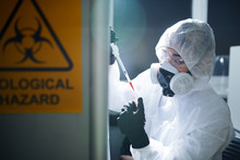 Concentrated Laboratory Scientist In Protective Workwear, Rubber Gloves, Goggles And Respirator Complying With Safety While Working With Infected Substance