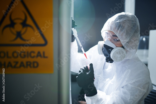 Fotografía  Concentrated laboratory scientist in protective workwear, rubber gloves, goggles