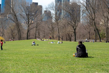 Central Park In New York City. People Sitting On A Green Lawn In Sheep's Meadow