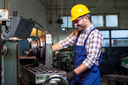 Fotografie, Obraz  Turner worker is working on a lathe machine in a factory