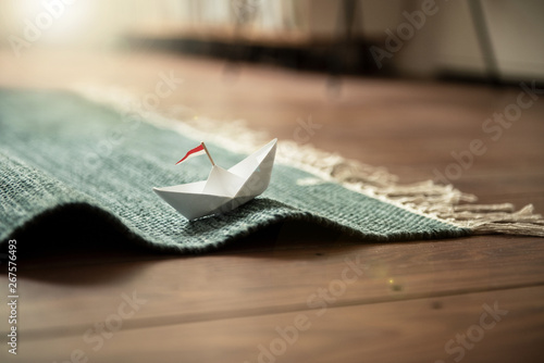 Fototapeta  Urlaub zu Hause | Papierschiff auf Teppich-Wellen