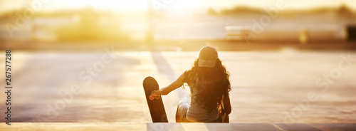 Rear view of young woman sitting with skateboard on steps at park during sunset panorama