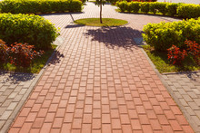 The Figure Track In The Park Is Lined With Concrete Tiles Of Two Colors.