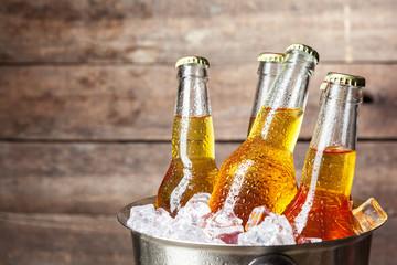 Hladne boce piva u kanti na drvenoj podlozi