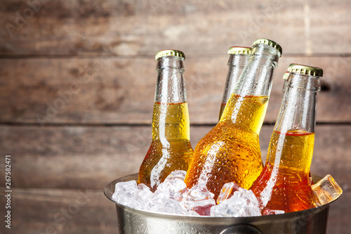 Cold bottles of beer in the bucket on the wooden background Canvas Print