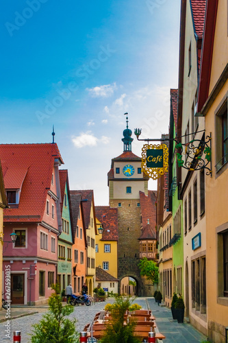 Fototapety, obrazy: Lovely view of a typical lane in Rothenburg ob der Tauber, Germany with colourful houses. The cobbled street Georgengasse leads to a gate tower with a clock and is called White Tower (Weißer Turm).
