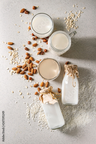 Variety of non-dairy vegan lactose free nuts and grain milk almond, hazelnut, coconut, rice, oat in glass bottles with ingredients above over white spotted background Canvas Print