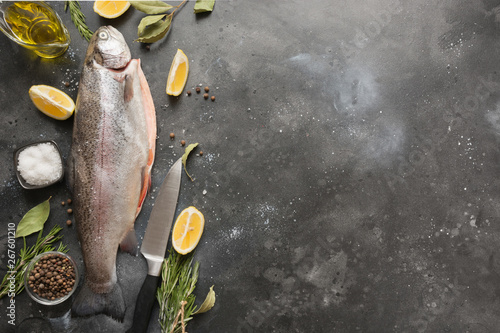 Fresh trout with aromatic herbs, spices on grey background Fototapeta