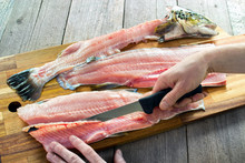 Filleting Trout , Removing Rib Bones With Sharp Fillet Knife On Wooden Board