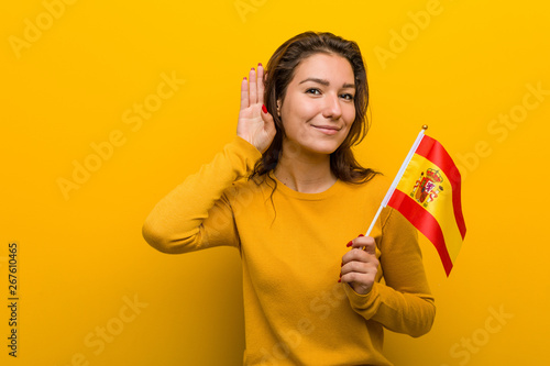Fotografie, Obraz Young european woman holding a spanish flag trying to listening a gossip