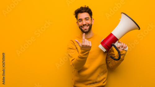Fotomural  Young man holding a megaphone inviting to come