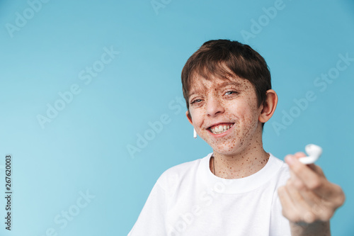 Image of attractive caucasian boy 10-12y with freckles wearing white casual t-shirt and earpods smiling at camera