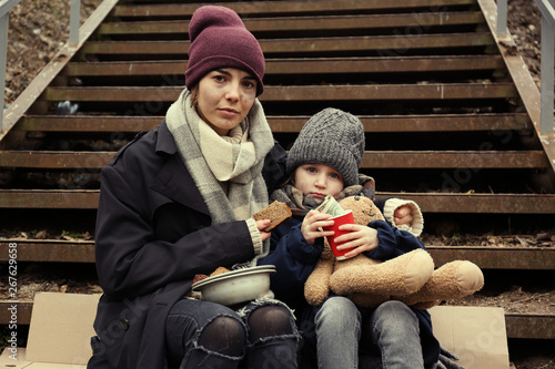 Poor mother and daughter with bread sitting on stairs outdoors Tapéta, Fotótapéta
