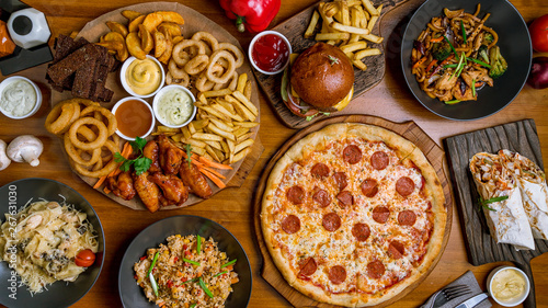 Assorted set from pizza Pepperoni, Assorted beer snacks, burger, wok and rice top view © bbivirys