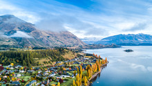 Small Town Surrounded By Yellow Autumn Trees On A Shore Of Pristine Lake With Mountains On The Background. Wanaka, Otago, South Island, New Zealand