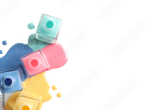 Valokuva  Spilled different nail polishes with bottles on white background, top view