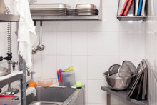 View Of Restaurant's Professional Washer, Sink, Brushes, Metal Shelving And Shelves With Kitchen Utensils, Cups, Cutting Board, Bowls, Lid, Buckets, Gastronomy Container Against White Tiled Wall