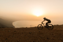 Spain, Lanzarote, Mountain Biker On A Trip At The Coast At Sunset