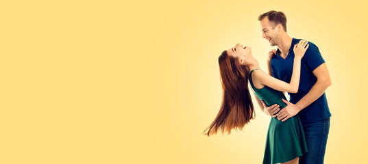 Photo of young happy dancing or hugging couple, with copy space, over yellow ...
