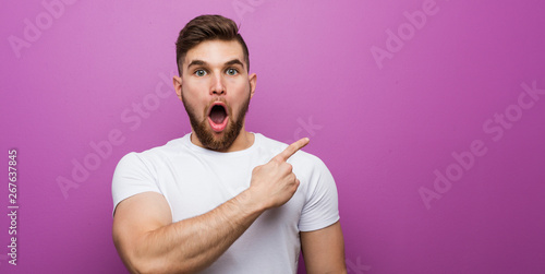Photo  Young handsome caucasian man pointing to the side