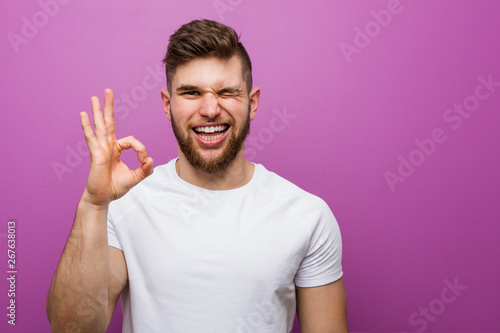 Fotomural  Young handsome caucasian man winks an eye and holds an okay gesture with hand