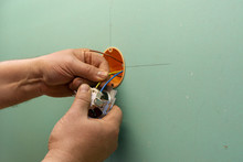 Hands Of Electrician Installing Electrical Socket