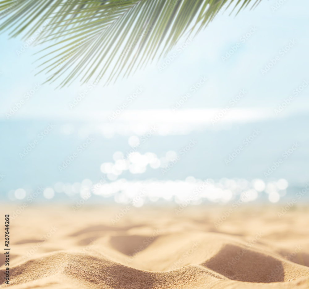 Fototapeta Sand with blurred Palm and tropical beach bokeh background, Summer vacation and travel concept. Copy space.