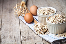 Fresh Chicken Eggs, Oat Flakes In Ceramic Bowls And Wooden Spoon On Rustic Wooden Table Background.