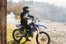 Motocross Driver On Motorbike With Smoke Coming Out Of Exhaust Pipe