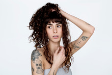 Portrait Of Tattooed Young Woman With Hand In Hair
