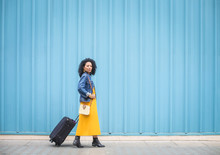 Woman Walking In Front Of A Light Blue Wall, Carrying A Luggage