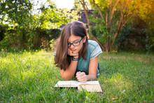 Girl Lying On A Meadow In Garden Reading Book