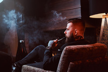 Bearded Handsome Man Is Sitting Near Fireplace And Smoking Hookah, Making Good Misty Vapour.