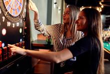 Two Women Playing Darts Setting Electronic Dartboard