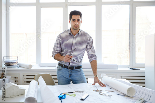 Portrait of handsome engineer posing at workplace an looking at camera, copy space