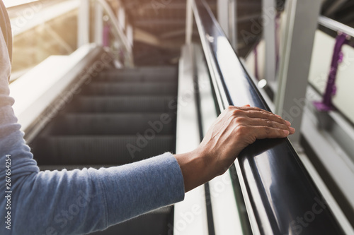 Woman's right hand on the escalator handrail on the train station Fotobehang