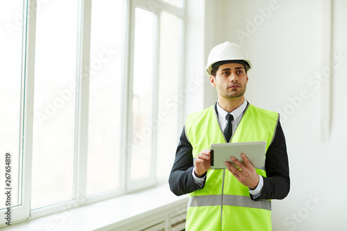 Fotografía  Waist up portrait of Middle-Eastern engineer wearing hardhat posing on construct