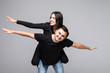 Young couple with hands arms like wings piggy-back ride walk highway adventures wear casual clothes isolated on grey background